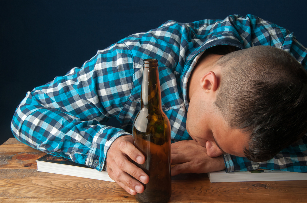 College student asleep on books with beer in hand because of binge drinking.