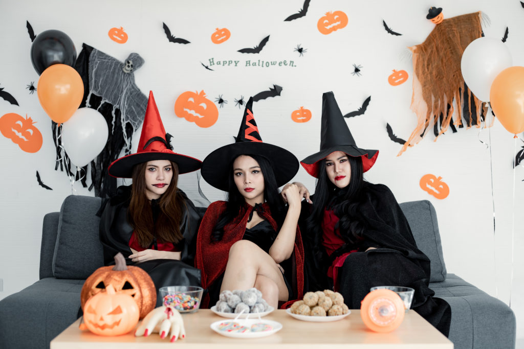 Three girls dressed as witches celebrating at a Halloween party.