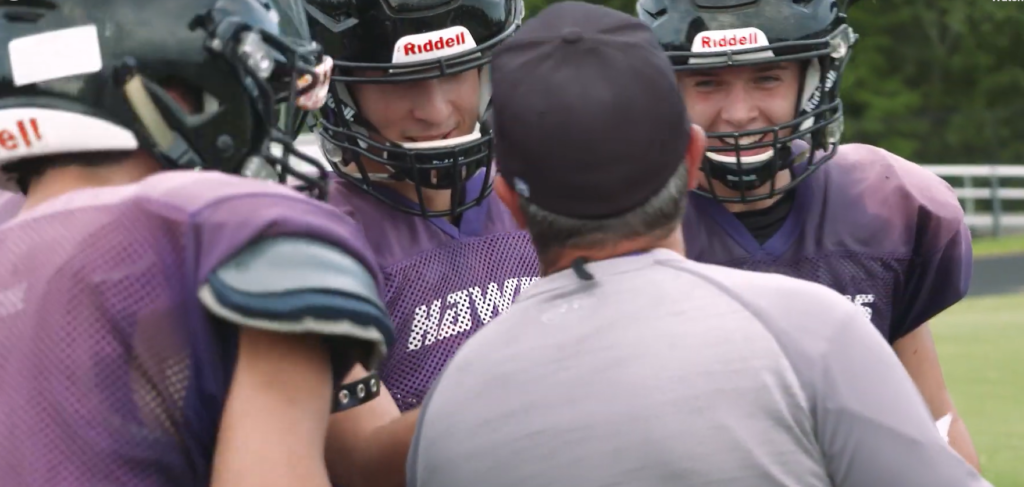 Football players talk with their coach about underage drinking.