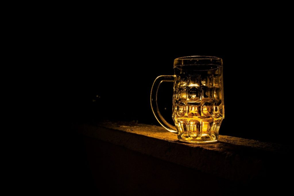 A mug of beer in a dimly lit room.