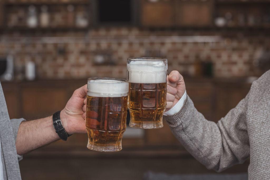 Two men toasting mugs of beer.