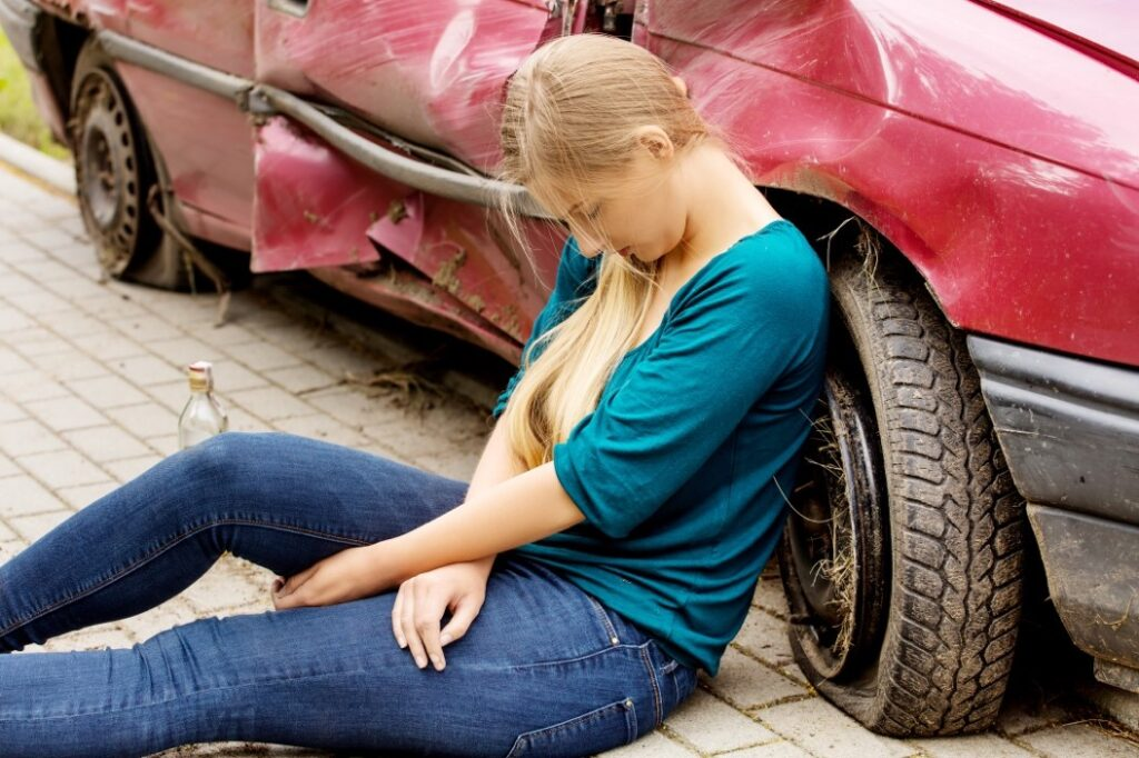 A teenage girl sitting down against a wrecked car.